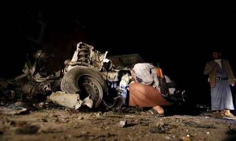 Homem observa carro em local de explosão de carro-bomba na capital do Iêmen, Sanaa.  17/6/2015.