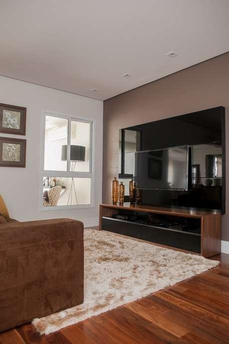Rack com pouca profundida e TV na parede ajudam a aproveitar o espaço restrito; teto branco, cores neutras e rodapé da cor da parede ajudam a dar amplitude ao ambiente