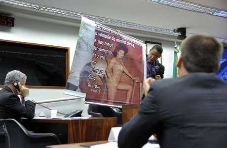 Pastor Joide Pinto Miranda mostra poster com foto de quando era travesti