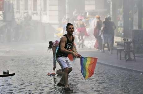 Participante de Parada Gay na Turquia reage enquanto outros fogem após a polícia ter usado canhões de água para dispersar o público