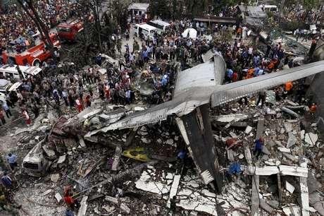 Forças de segurança examinando os destroços da aeronave C-130 Hercules, na cidade de Medan, na Indonésia