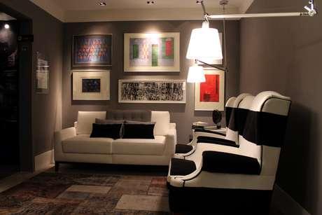 Tom escuro das paredes destaca as obras de arte e os móveis do Gabinete de Paula Lino