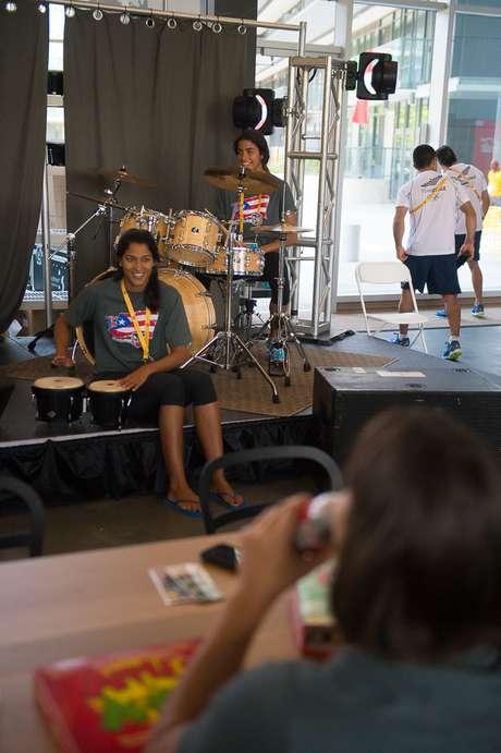 Atletas tocam instrumentos musicais em lounge dentro da Vila