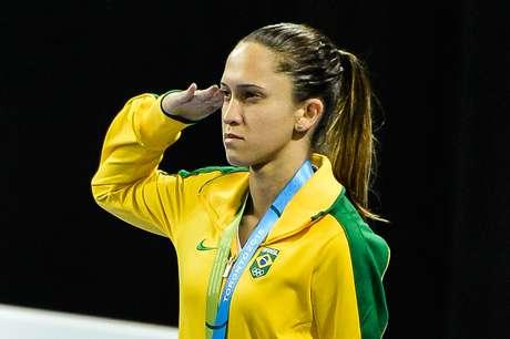 Iris Sing presta continência com medalha de bronze no pódio