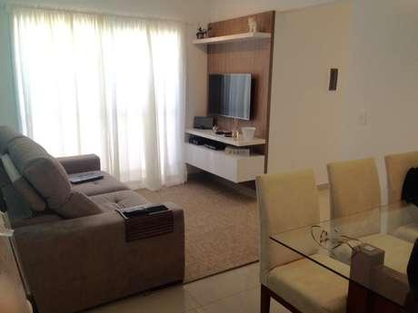 Arquiteta sugere mix de quadros na parede de frente para a TV e xale terroso no sofá para deixar o ambiente mais acolhedor