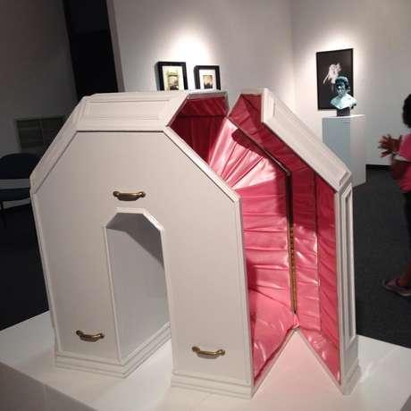 """Caixão na exposição onde se lê o nome de Rosalie, seu ano de nascimento e uma inscrição que diz algo como """"impressione a morte""""."""