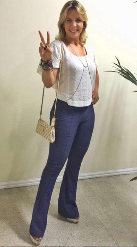 Carla Perez usa calça azul, tipo flare, com blusa branca curta. A calça marca mais do que devia e o comprimento da blusa acaba valorizando demais os quadris. A bolsa pequena e o colar, conhecido como body chain, estão fora de contexto no look