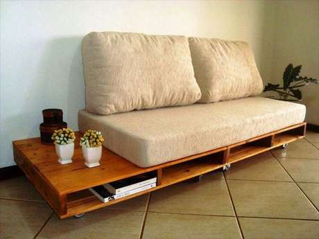 O suporte do sofá é feito com pallets, que apresentam nichos para guardar revistas