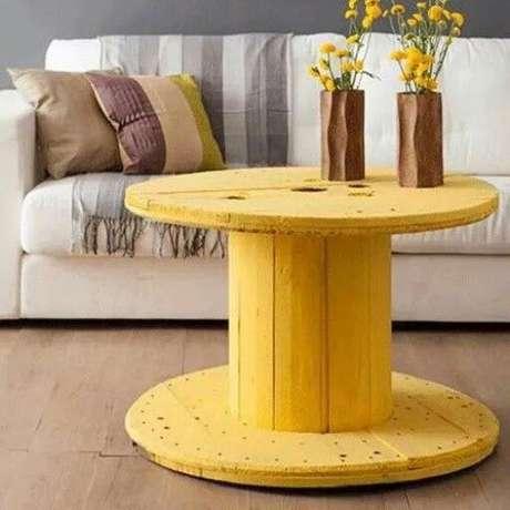O carretel pintado de amarelo se transformou em uma mesa de centro