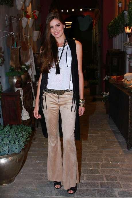 Camila Queiroz aposta na calça flare, camiseta básica branca, colete preto e acessórios anos 70: como as cores são neutras, o estilo não pesa muito