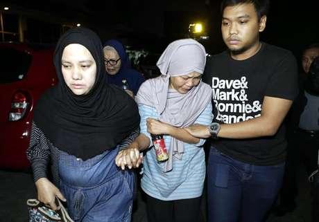 A mãe de um membro da tripulação Trigana Air avião desaparecido (ao centro) chora enquanto anda fora do escritório principal Trigana Air, em Jacarta, Indonésia