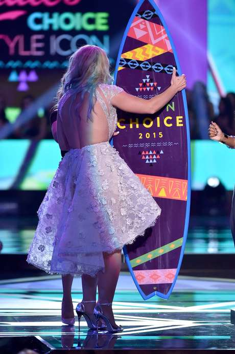 Vendo de trás, com as costas à mostra, parece que Britney está meio apertada no modelito, cujo corte da saia amplia demais os quadris.