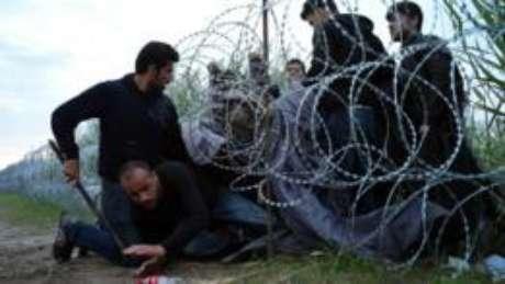 Na cidade de Roszke, na Hungria, imigrantes que chegam pela fronteira com a Sérvia tentam desesperadamente cruzar uma cerca de arame para seguir até a Alemanha