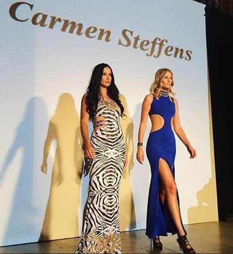 Adriana Lima, com longo em animal print estilizado, ao lado da alemã Toni Garnn, que exibe vestido azul com recorte na cintura e fenda
