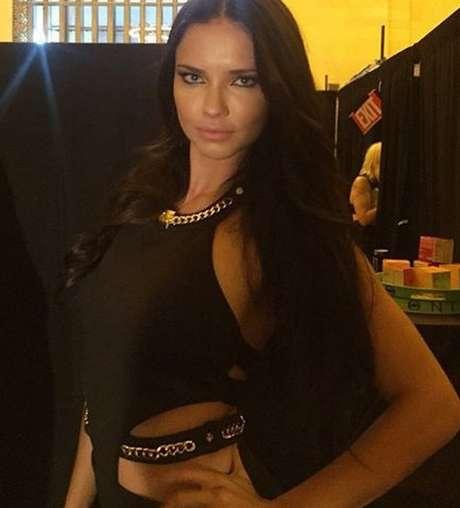 Adriana Lima no backstage do desfile em Nova York: correntes douradas adornam vestido preto exibido pela top