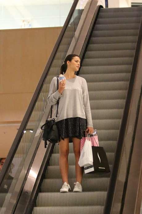 Bruna Marquezine veste look bem jovem e ideal para seus 20 anos. O visual composto por saia curta com moletom e tênis é prático, confortável e despojado. Bela opção.