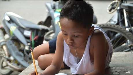 Foto muda vida de menino que estudava sob luz do McDonald's