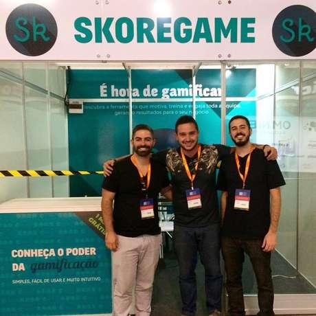 Gabriel Falcione (à esquerda), fundador da startup criadora da Skoregame, à frente de um estande da vendas da plataforma