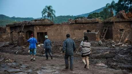 Pessoas andam em meio à destruição causada pelo rompimento da barragem da Samarco em Mariana, em 2015