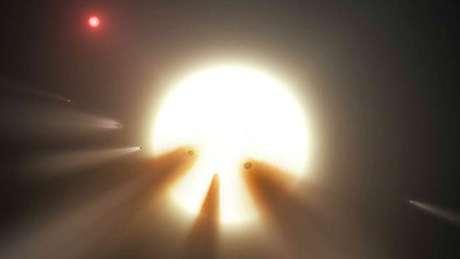 Ilustração mostra uma estrela atrás de um cometa fragmentado; observações sugerem que esse seja o motivo dos misteriosos padrões de luz da estrela KIC 8462852