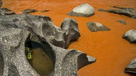 Resíduos em trecho pedregoso do rio Doce em Minas Gerais; no lado esquerdo, pode-se observar a cor original da água, empoçada na rocha