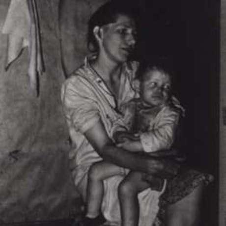 Menina com malária no colo da mãe; ocorrência da doença era crônico no sul dos EUA