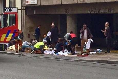 Equipes de emergência socorrem feridos em frente à estação Maelbeek do metrô, em Bruxelas