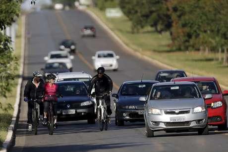 Presidente do Brasil Dilma Rousseff monta sua bicicleta acompanhados por seguranças perto do Palácio da Alvorada, em Brasília
