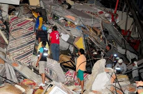Grupo de pessoas busca sobreviventes nos escombros de um edifício em Manta, Equador.