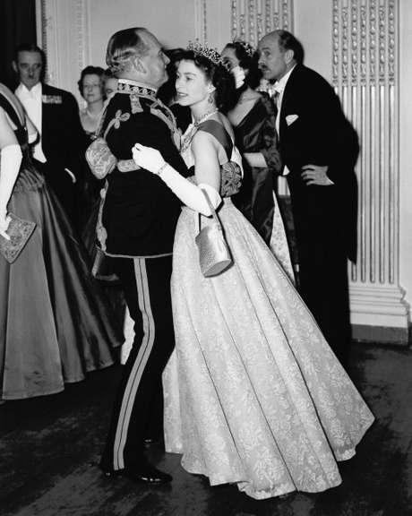 Rainha Elizabeth II dançando com Marechal Sir John Baldwin (1892 - 1975) em um baile realizado no Hyde Park Hotel, Londres, em 26 de novembro de 1954.