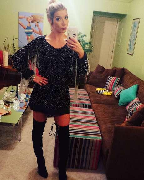 Cantora usou um vestido preto e curto para assistir ao desfile de Helo Rocha