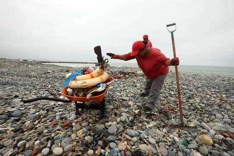 """Uma trabalhadora de limpeza recolhe restos plásticos e outros materiais de construção que são """"cuspidos"""" diariamente pelo oceano Pacífico à praia Carpayo, situada no Callao, a cidade portuária de Lima"""