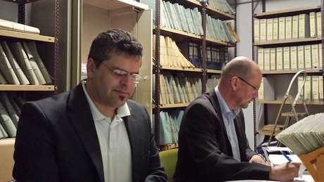 Jens Rommel (à esq. na foto) em trabalho em arquivos; pesquisador também visitou o Brasil à caça de nazistas