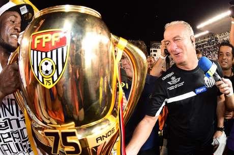 Dorival Júnior sorri ao lado da taça e campeão paulista