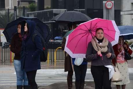 Pedestre se protege do frio e da garoa na avenida Paulista, em São Paulo (SP), na manhã desta terça-feira (24)