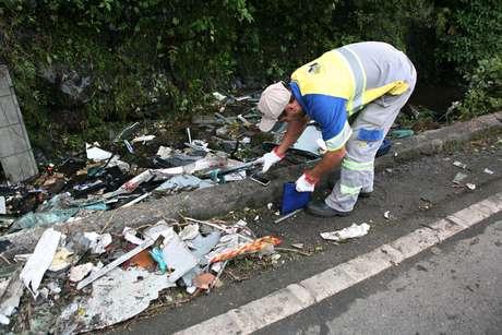 Funcionário da rodovia recolhe pertences das vítimas do acidente