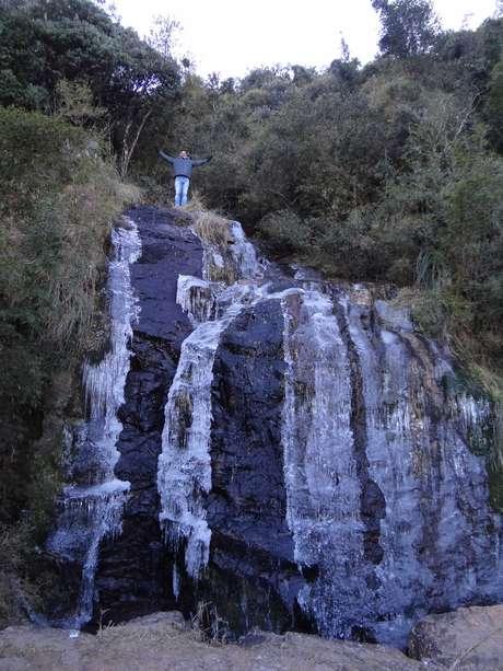 Turista escala cachoeira congelada em Urupema, na região serrana de Santa Catarina
