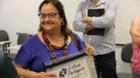 A professora Tânia Regina Oliveira Ramos recebeu os documentos e o livro