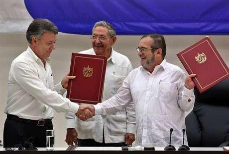 O delegado das Farc em Cuba, Rodrigo Londoño Echeverri (dir.), e o presidente da Colômbia, Juan Manuel Santos (esq.), junto ao presidente de Cuba, Raúl Castro, seguram o acordo de paz entre o governo e a guerrilha durante cerimônia em Havana
