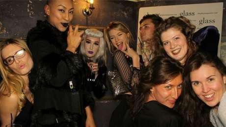 Evie (segunda à dir.) em uma festa com amigos, dos quais apenas reconhece um