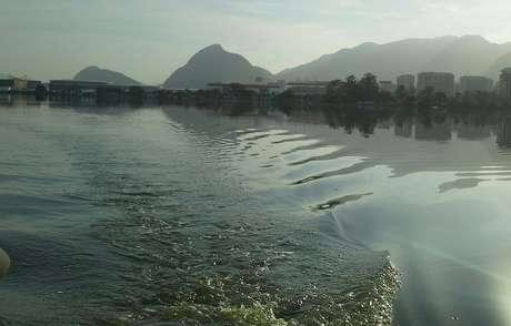 As águas da Lagoa de Jacarepaguá chegam a ficar gelatinosas por causa do esgoto; ao fundo, o Parque Olímpico
