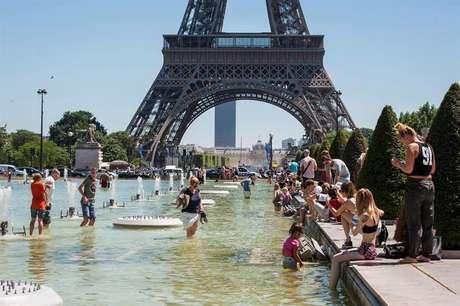 Multidão se refresca nas fontes dos jardins da Torre Eiffel, em Paris. A agência meteorológico alertou para as altas temperaturas em boa parte da França. Imagem de 19 de julho de 2016.