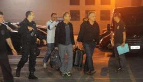 O ex-diretor da Delta Cláudio Abreu (de branco), o empresário Adir Assad (de jaqueta) e o empresário Carlinhos Cachoeira (de preto) entram na viatura da Polícia Federal após depoimento