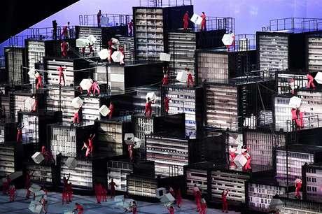 Dançarinos escalam réplicas de prédios representando as metrópoles brasileiras