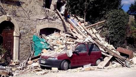 Carro é atingido por escombros após terremoto em Arquata del Tronto, na região central da Itália