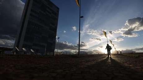 Mulher passa pelo Congresso Nacional, em Brasília, na terça-feira (30); imprensa estrangeira destaca problemas à frente no cenário pós-impeachment