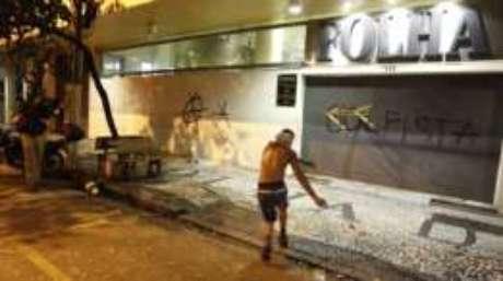 Homem atira cavalete contra a fachada do jornal Folha de S.Paulo, que também foi alvo de protestos nesta semana