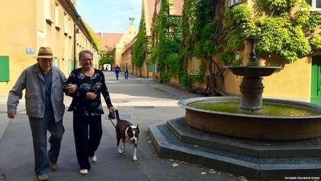 Vizinhos Ilona Barber e Friedrich Fischer passeiam em Fuggerei, na cidade alemã de Augsburg