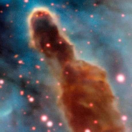 Região R18 da nebulosa de Carina: pontos rosa são estrelas que ainda estão dentro da nuvem de poeira original