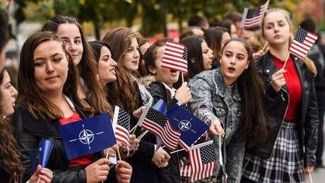 Jovens em Kosovo mostram bandeiras dos EUA e da Otan durante competição do Exército americano e da força de segurança de Kosovo em Pristina. Aproximadamente 4.600 soldados liderados pela Otan ainda estão presentes no Kosovo